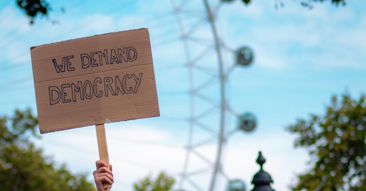 """Papschild mit Aufschrift: """"We Demand Democracy"""""""