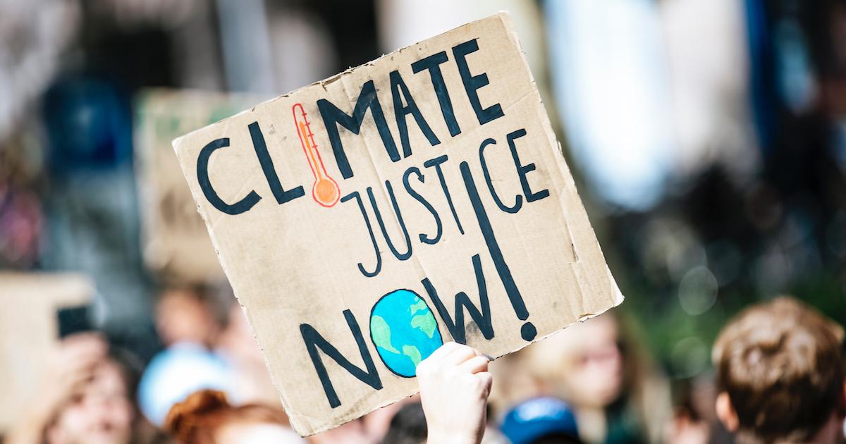"""Pappschild mit klimapolitischer Forderung: """"CLIMATE JUSTICE NOW!"""""""